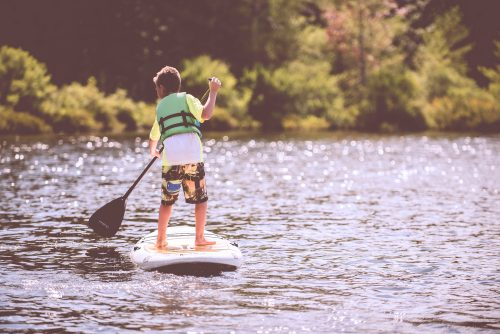 A young boy paddle boarding