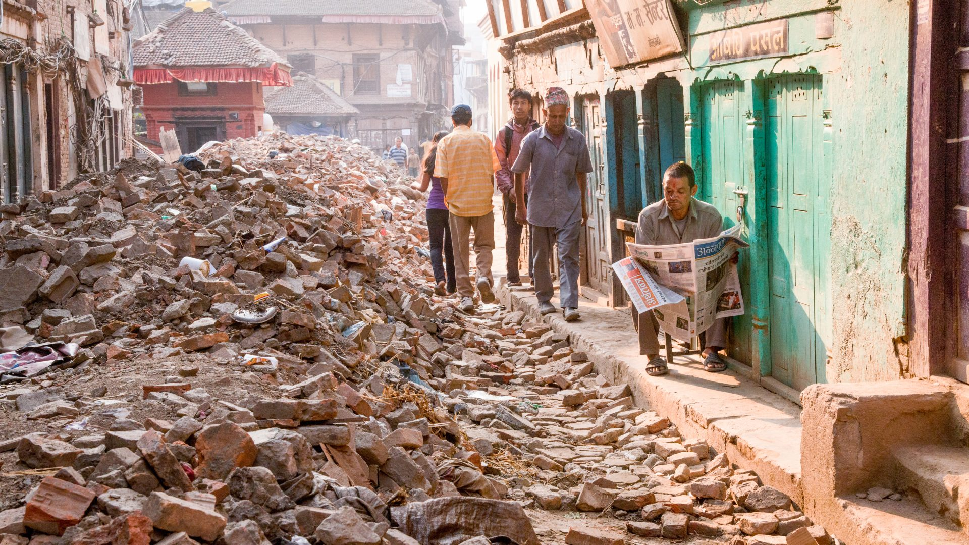 Man sits in front of his shop reading as life goes on around him after the Nepal earthquake in 2015.