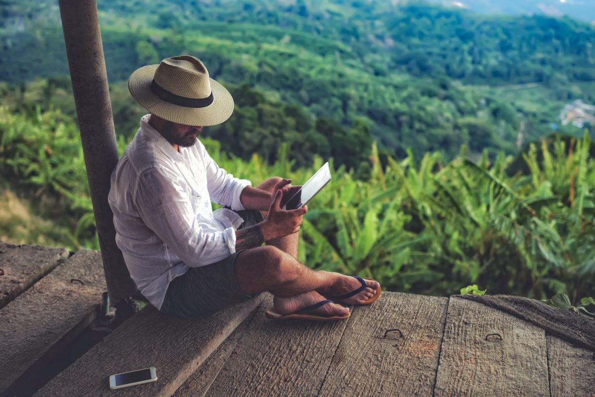 Digital detox: A man looks at his device as the green valleys fall away below him.