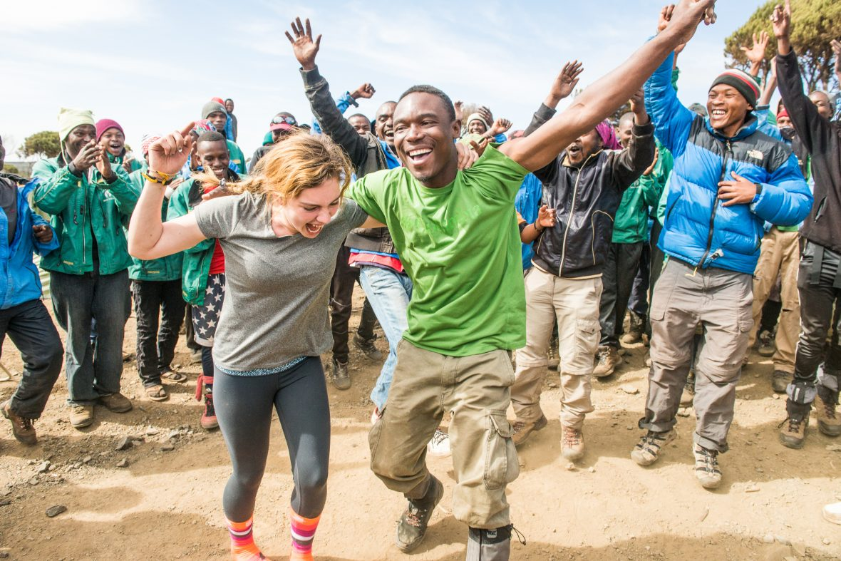 A tourist in Tanzania is jubilant and dances around with the crew from her hike.
