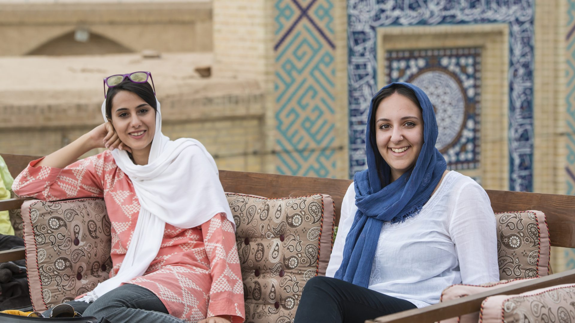 Two women sit together at a rooftop cafe in Iran.