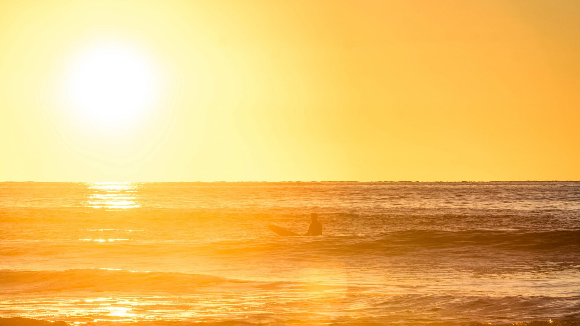A surfer takes in the sunset on Vancouver Island.