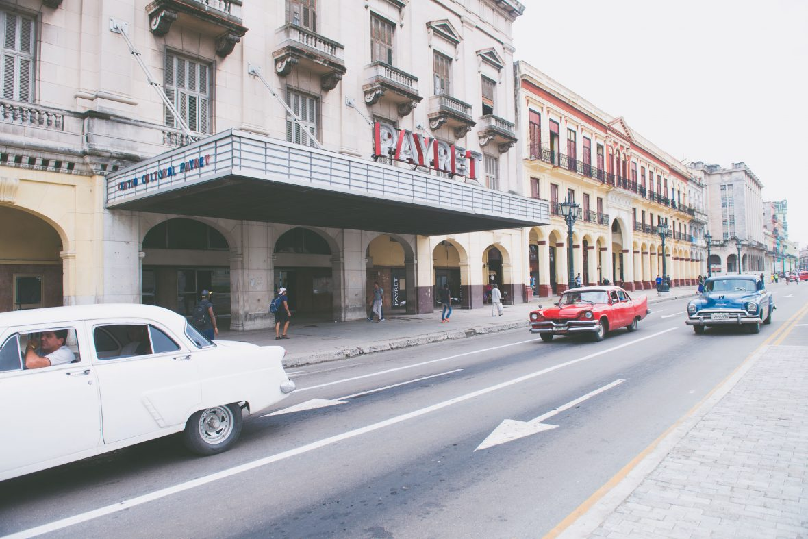 Old cars drive down one of the main streets in Havana, Cuba.