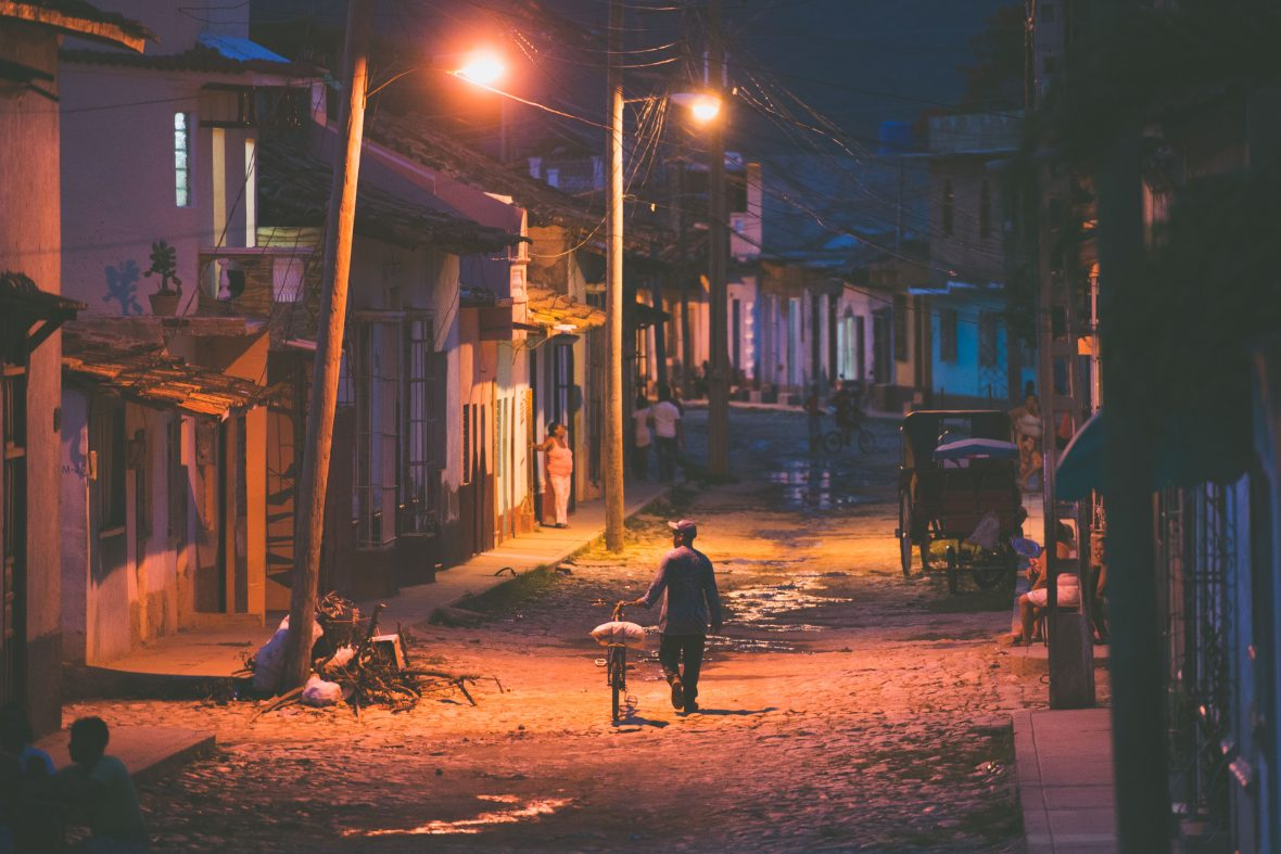 As night falls a lone man with a bicycle passes under the street lights of Trinidad in Cuba.