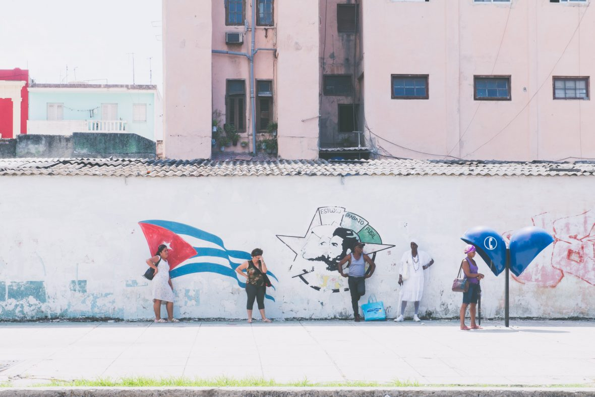 Locals in Havana, Cuba, line a wall painted with a Cuban flag and revolutionary slogans.