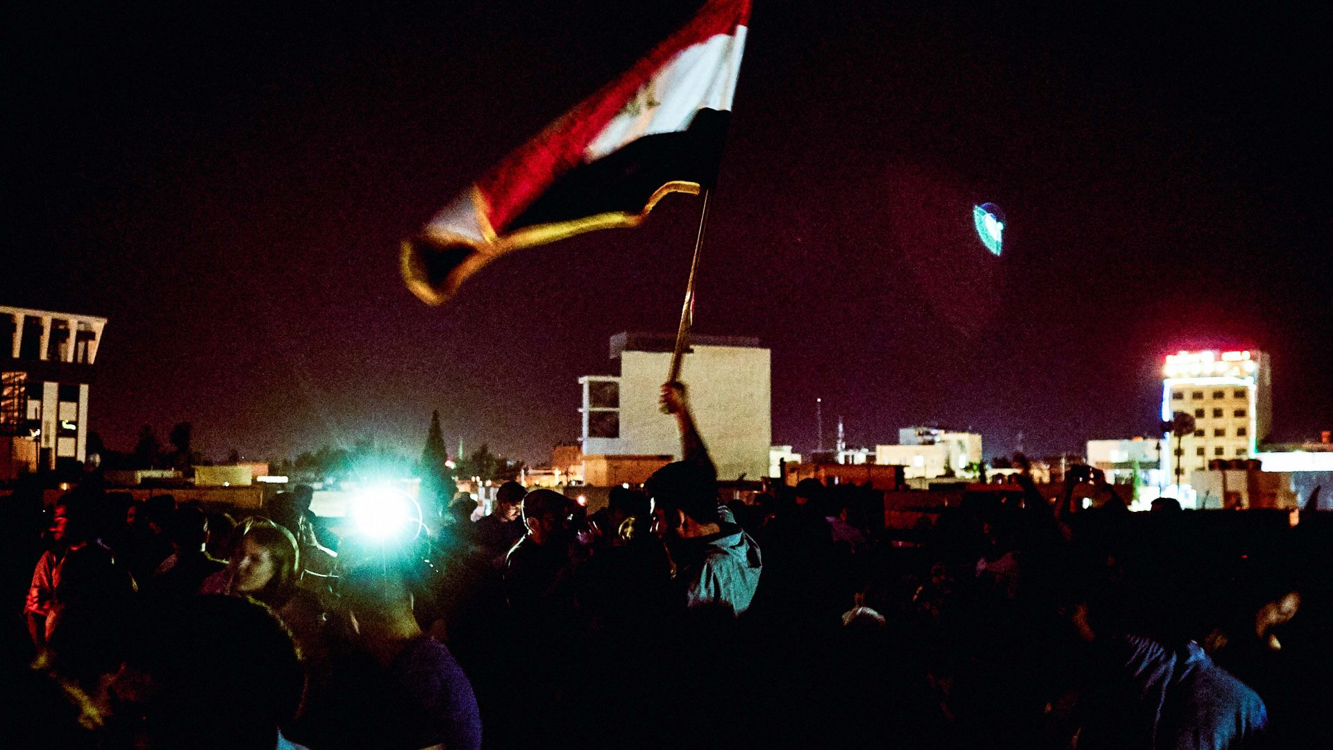 A man can be seen raising the Iraqi flag at an event in Erbil, Iraq.