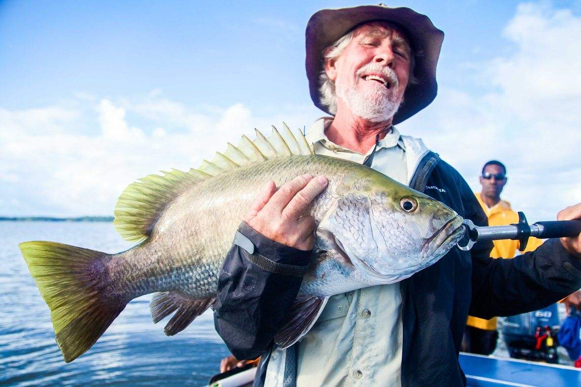 A tourist holds onto his catch during a fishing expedition to Lake Murray, PNG.