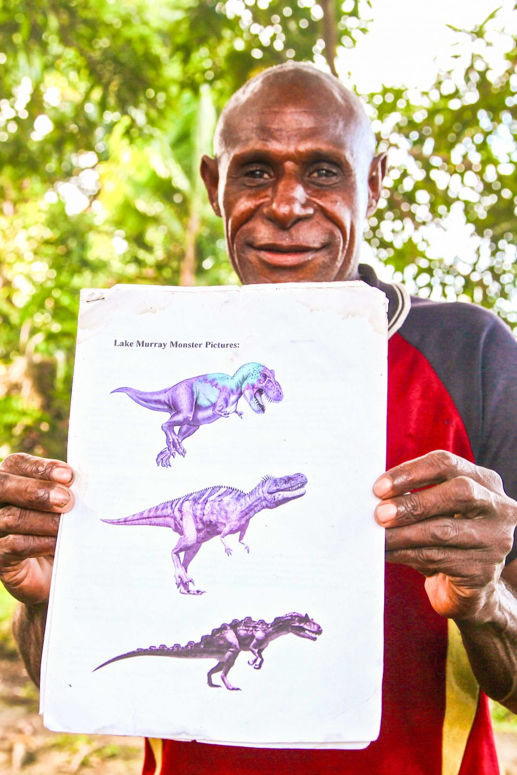 A local shows pictures of the monsters that are believed to be lurking beneath the waters of Lake Murray in PNG.