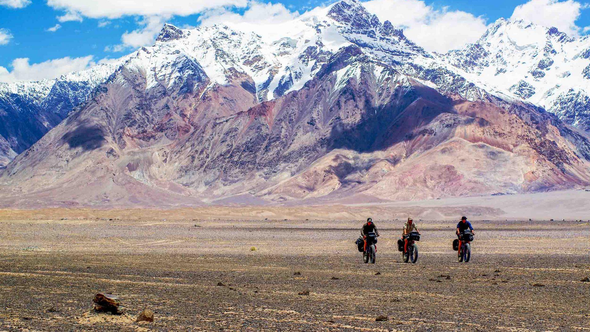 Three men cross through the Pamir Mountain range on mountain bikes.