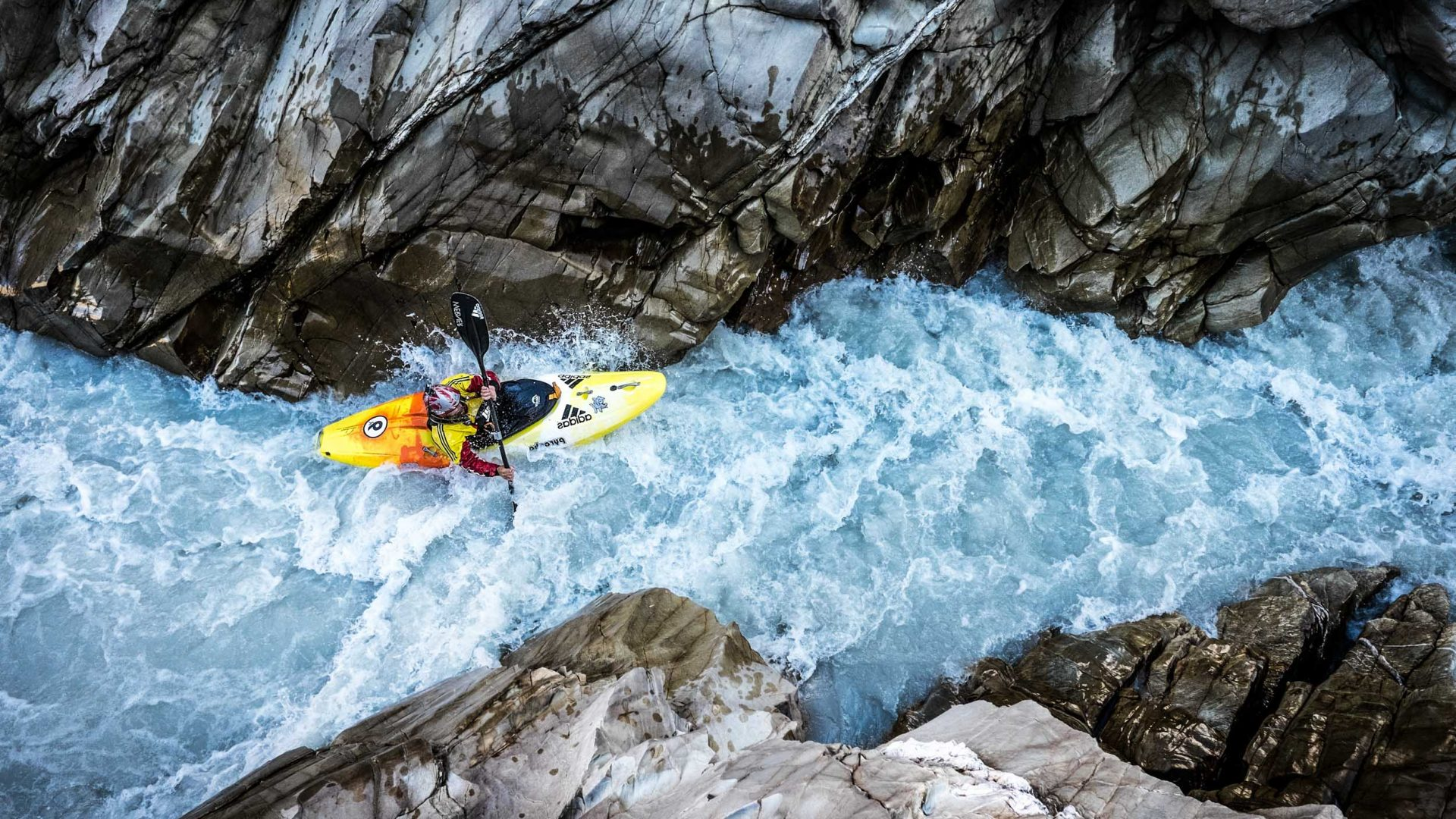 Kayaking down a rough and narrow gorge.