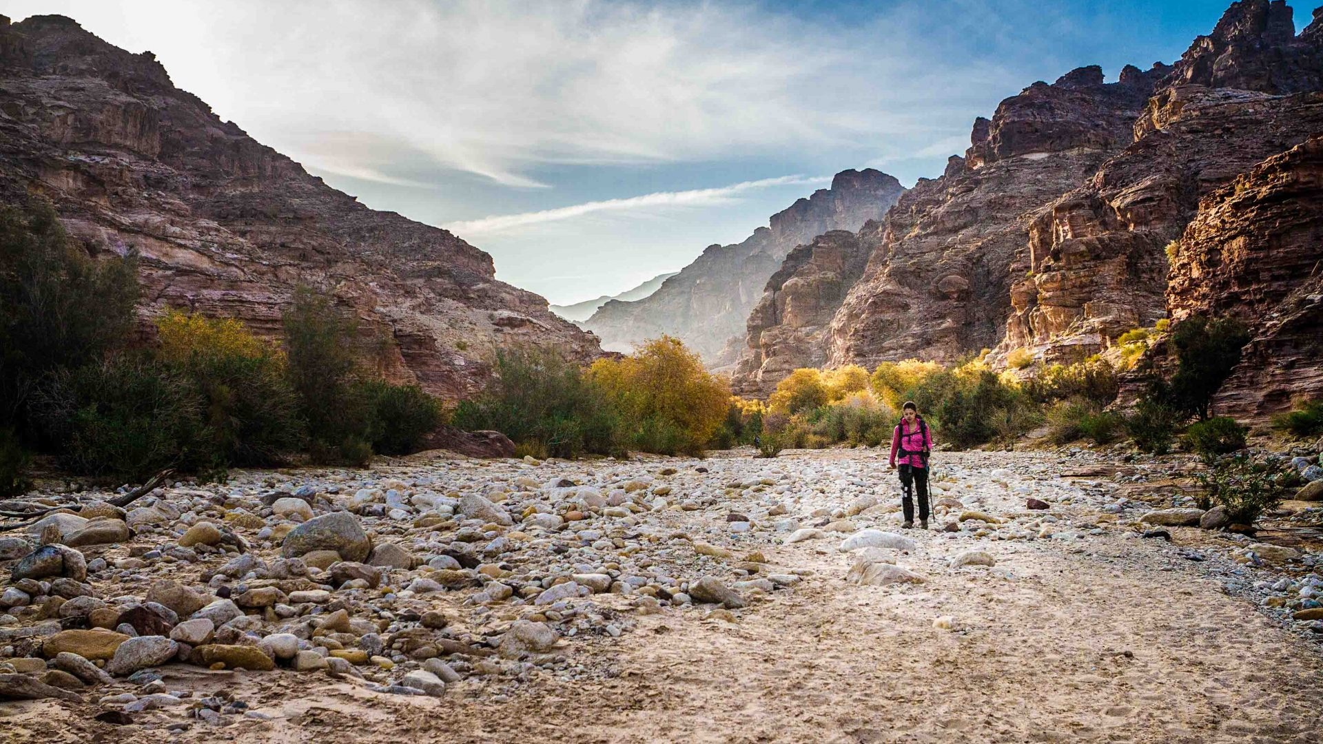 A hiker is framed by mountains during the hike along the Jordan trail, from Gaa Mriebed to Wadi Gseib along the Jordan Trail.
