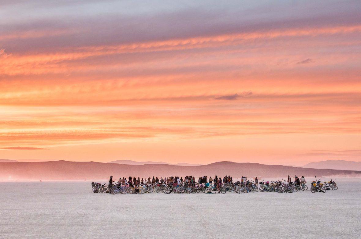 Attendees at Burning Man marvel as the sunset turns the sky into vibrant hues of orange.