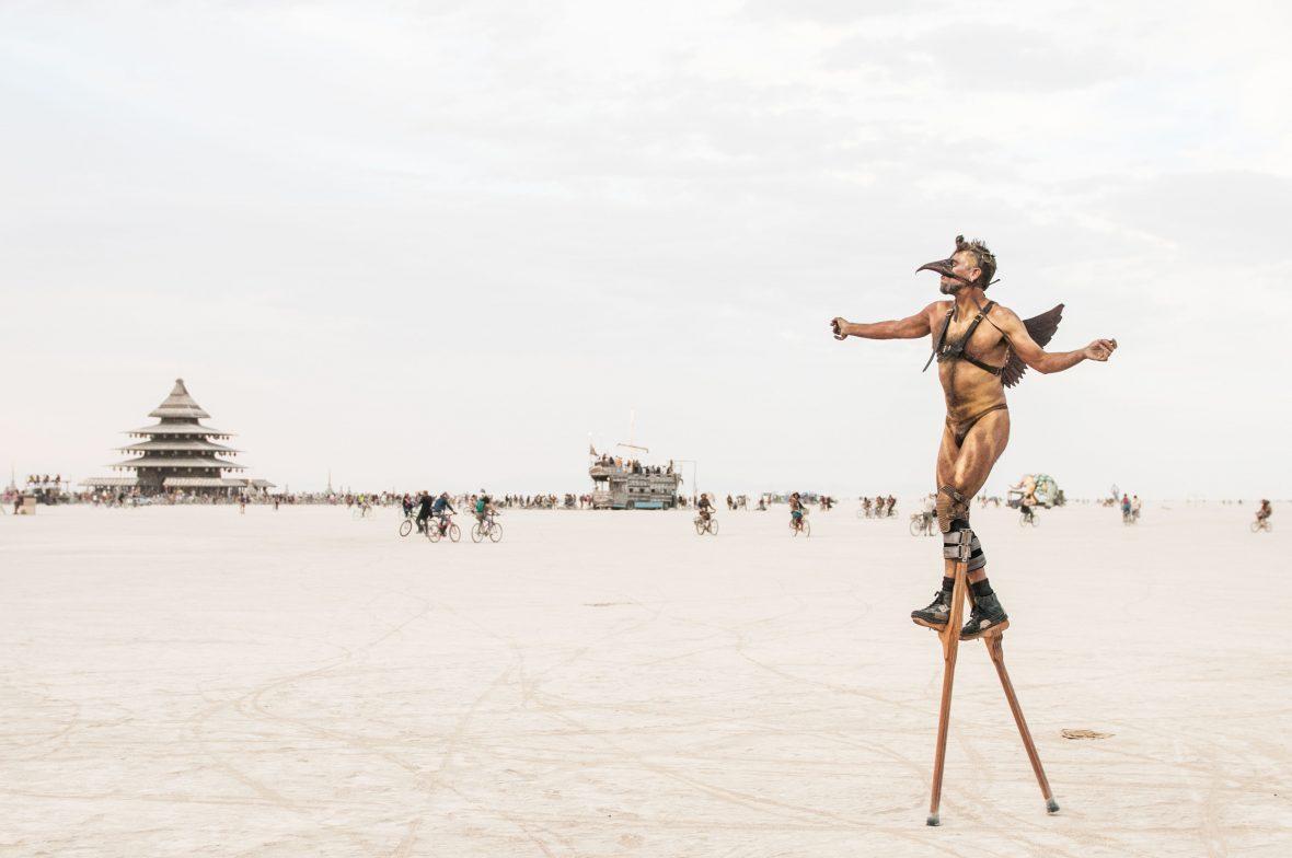 A man walks on stilts across the dusty playa of Burning Man.
