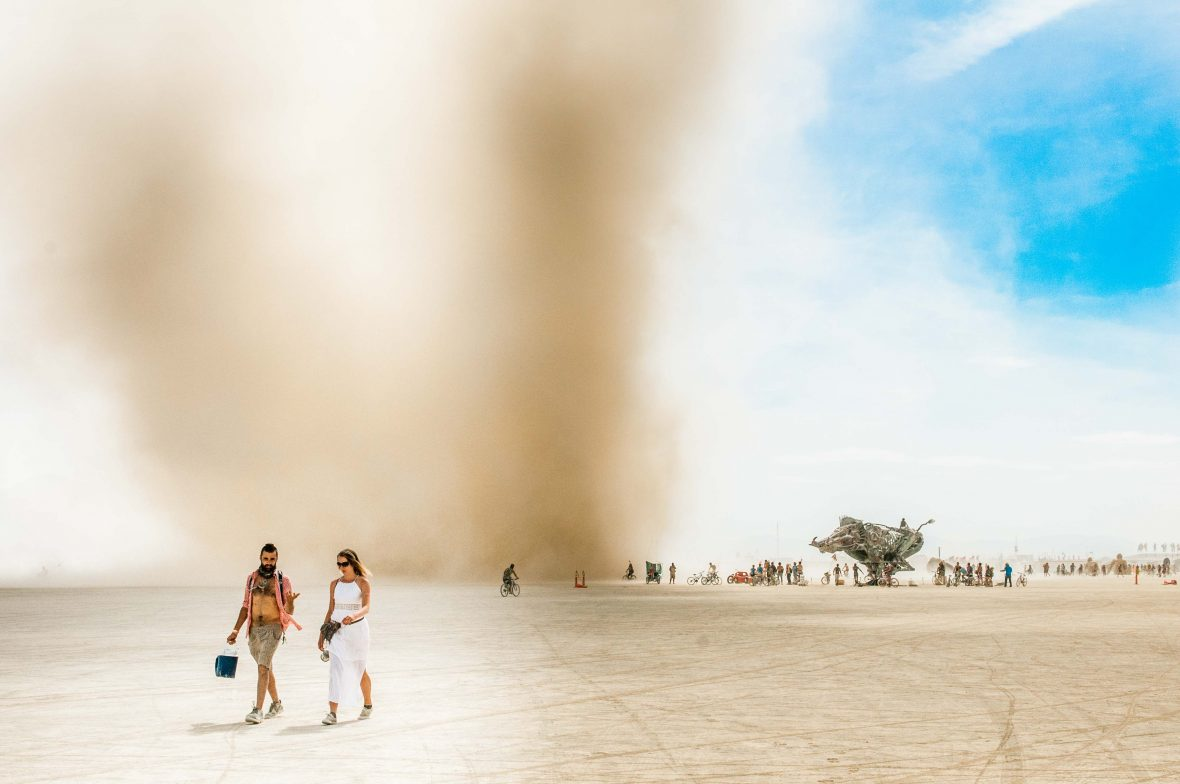 Two people walk through the playa of Burning Man, seemingly oblivious to the dust storm coming up behind them.