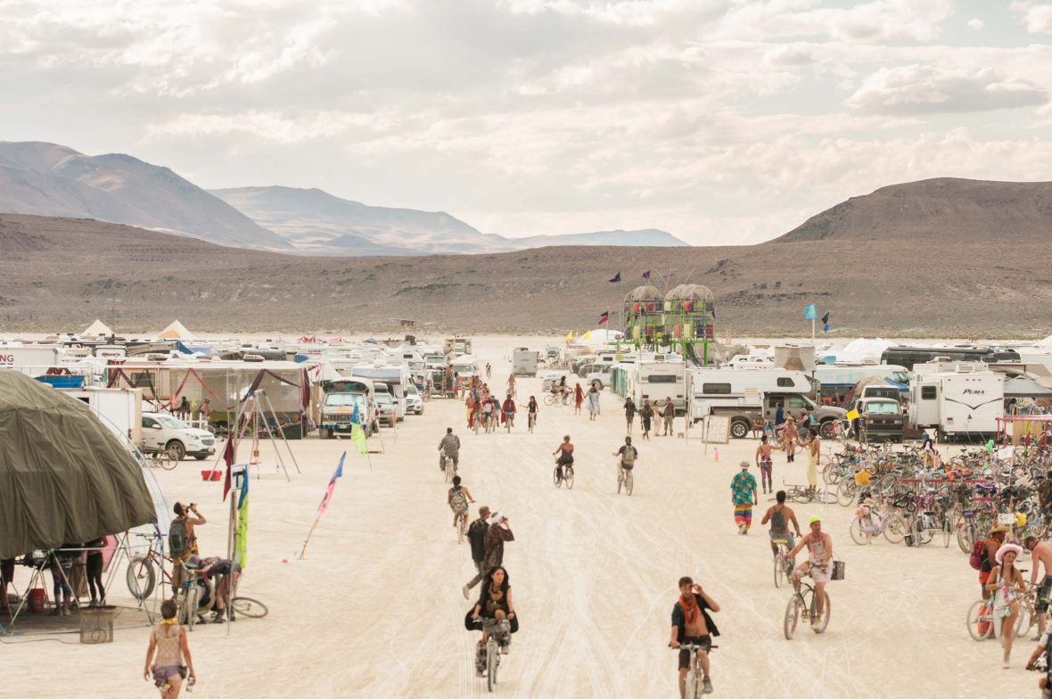 One of the streets leading through the camps at Burning Man is buzzing with people on foot and on bikes.
