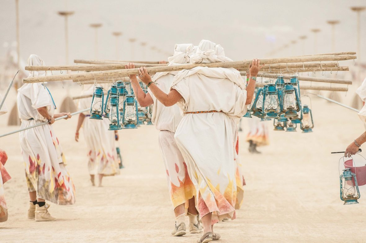 Lantern carriers make their way through the dusty streets before dusk each day at Burning Man.