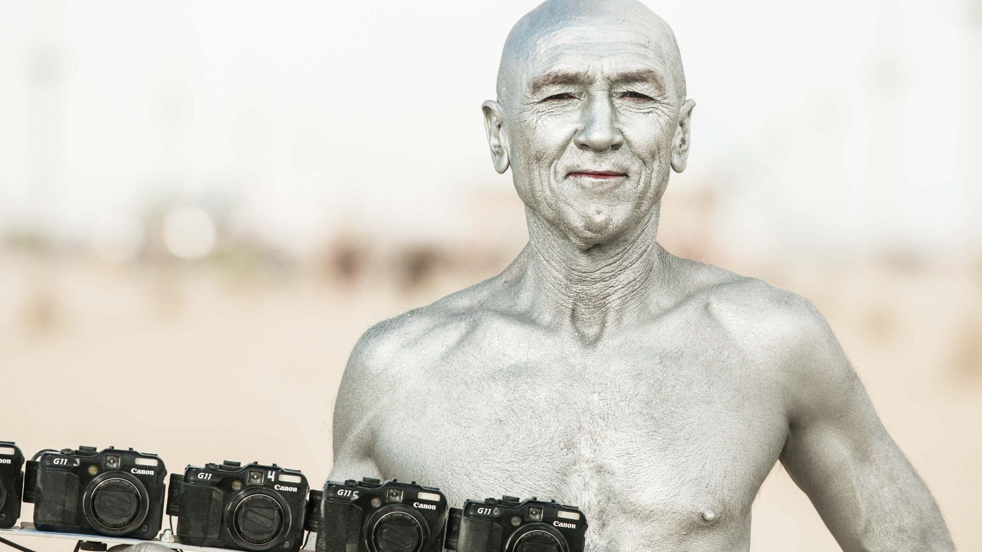 A man painted in silver presents a row of cameras at Burning Man.