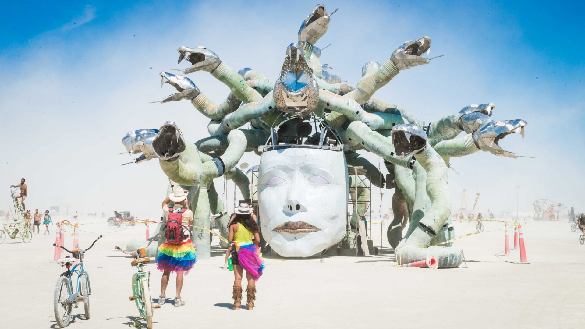 A couple in rainbow tutus looks at an art installation at Burning Man.