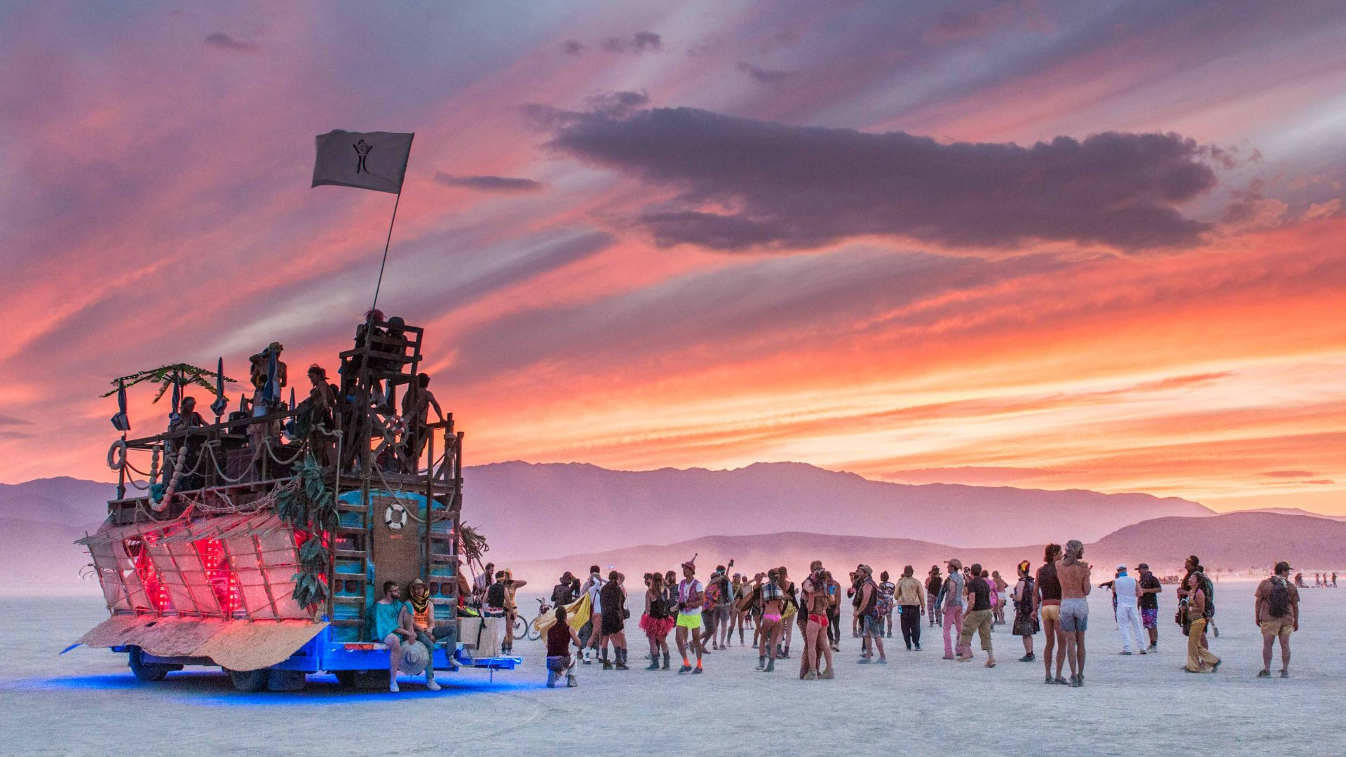 As the sun sets over Burning Man, an art car stands tall over attendees down below.