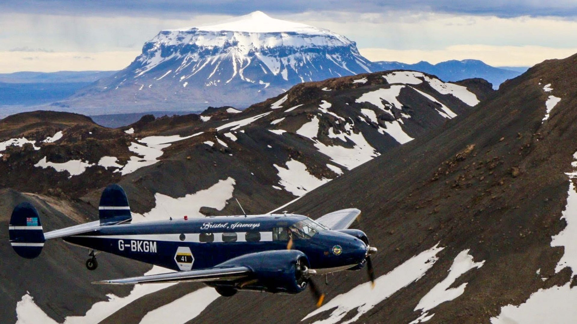 A plane flies above the snowy mountains in Iceland.