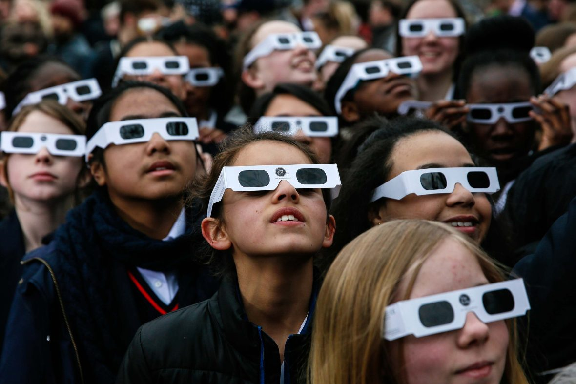 School children wearing protective glasses during a solar eclipse.