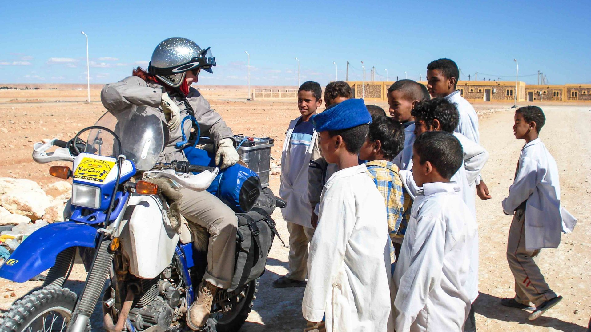 Lois pauses during a motorcycle ride to talk with kids in Algeria.