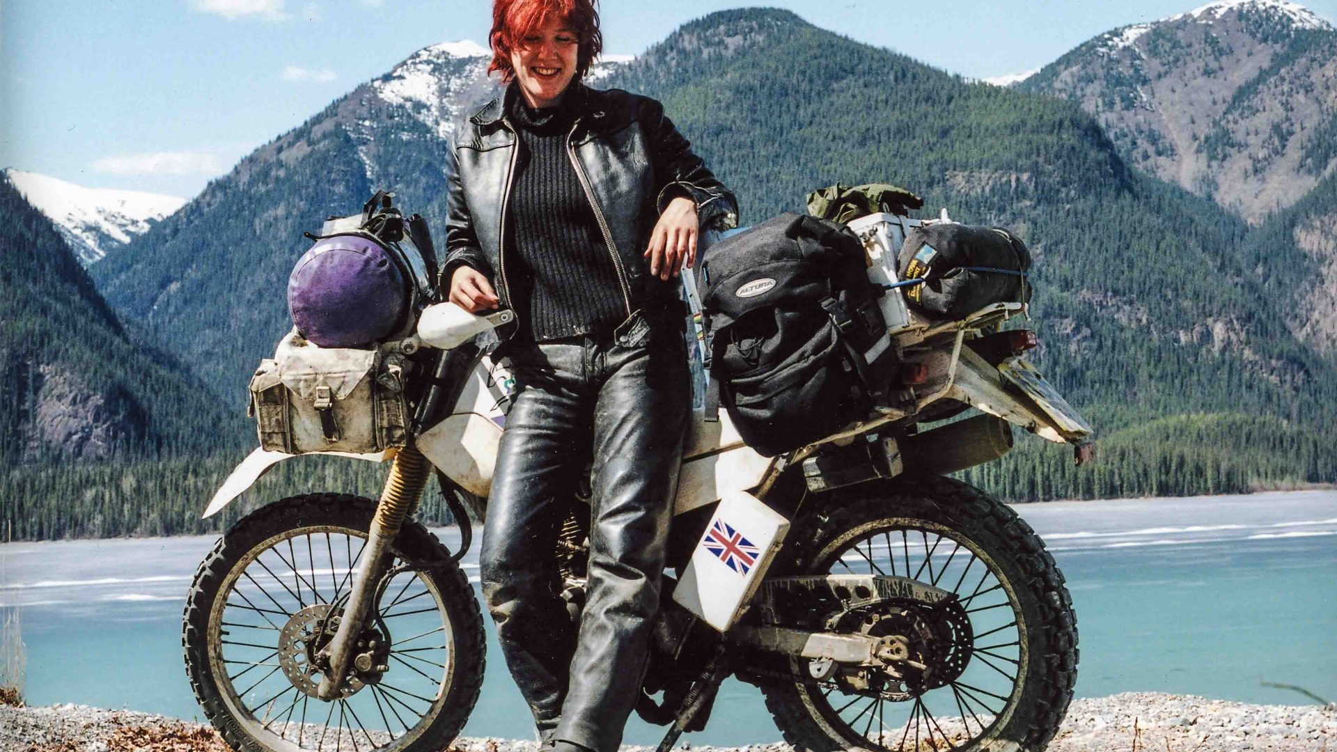Lois pauses with her motorcycle at a lake in Canada.