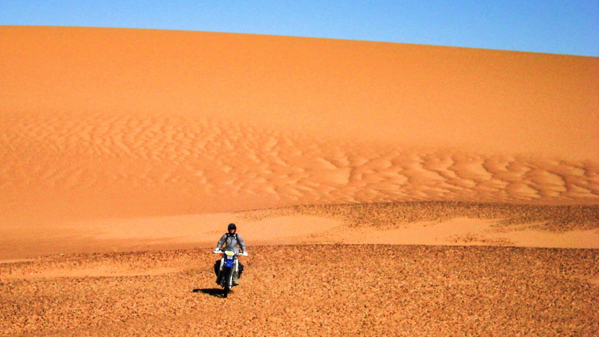 Lois rides her motorcycle across orange sand dunes in Niger.