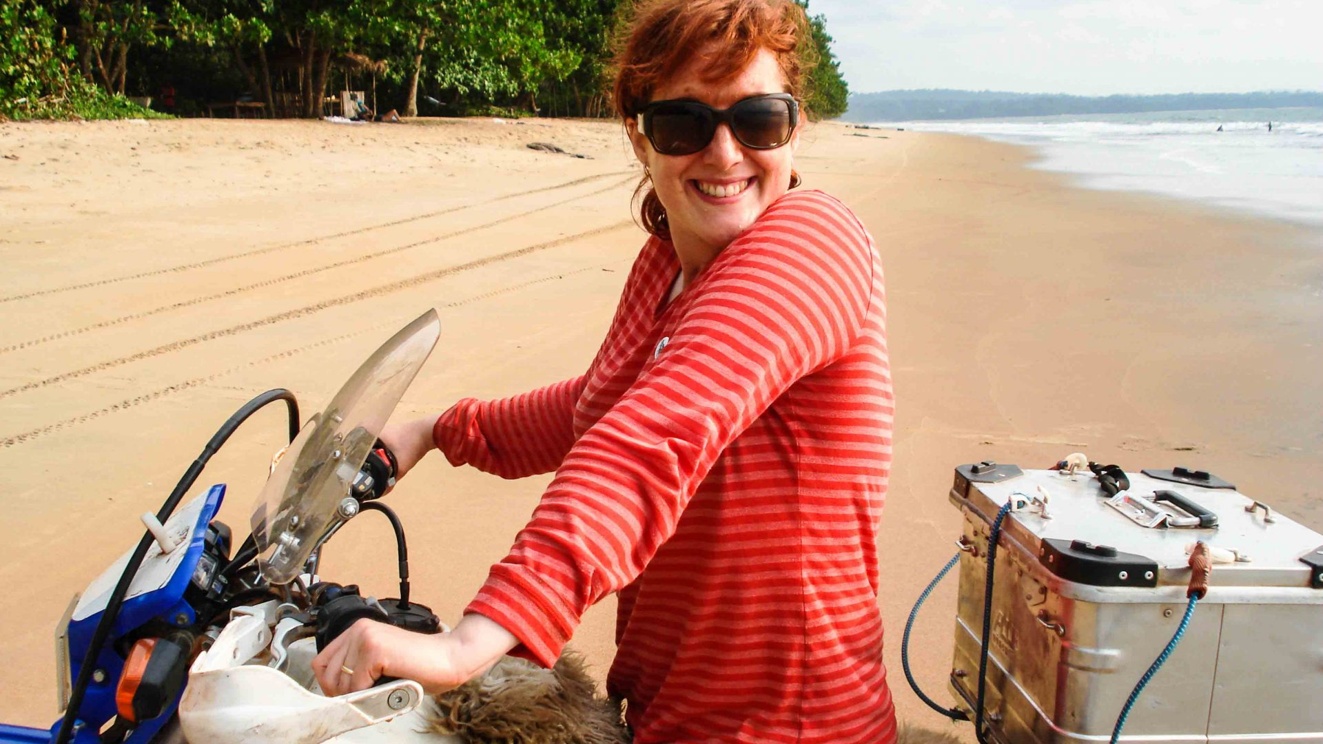 Lois poses for a photo on her bike at a beach in Cameroon.