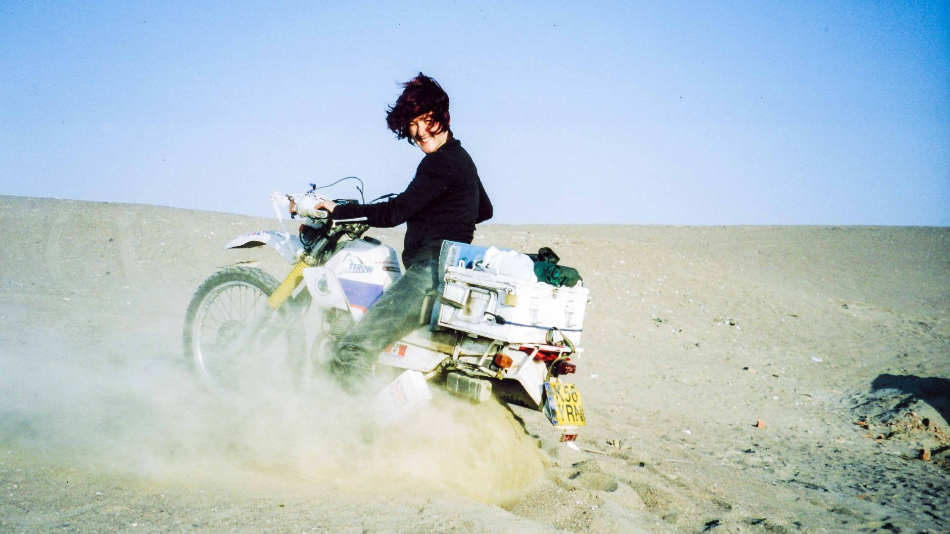 Lois rides her motorcycle through the desert in Peru.