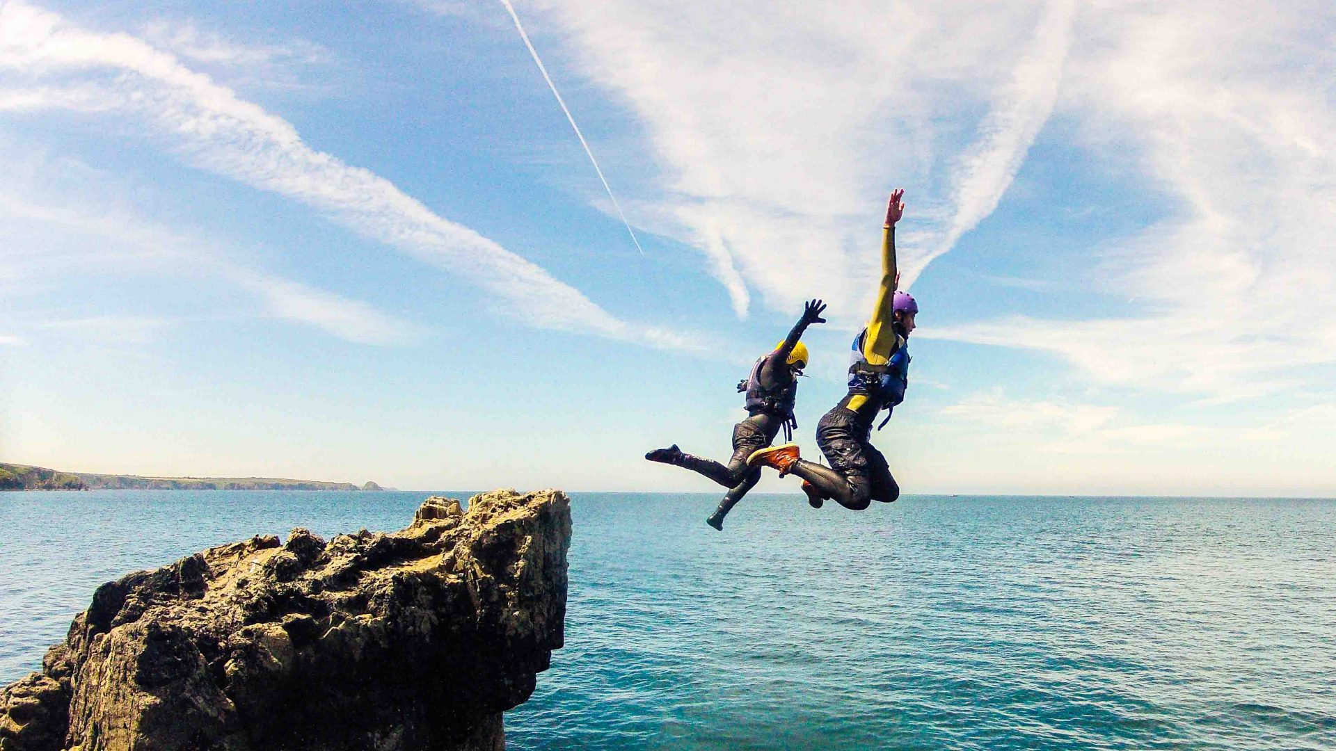 A couple of people jump from a rock ledge to the water during this coasteering adventure.