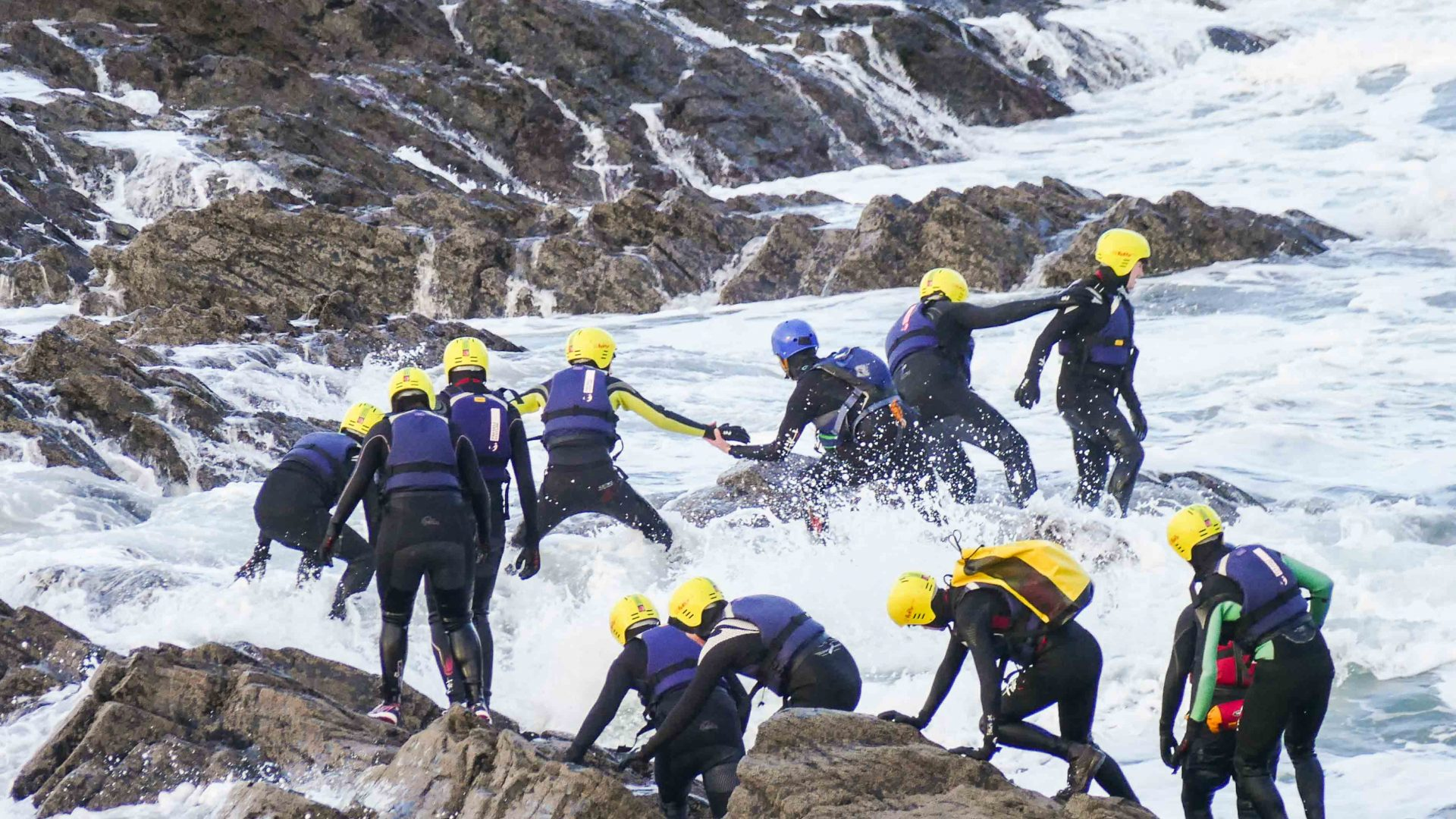 Clients on a coasteering adventure make their way carefully across the rocks.