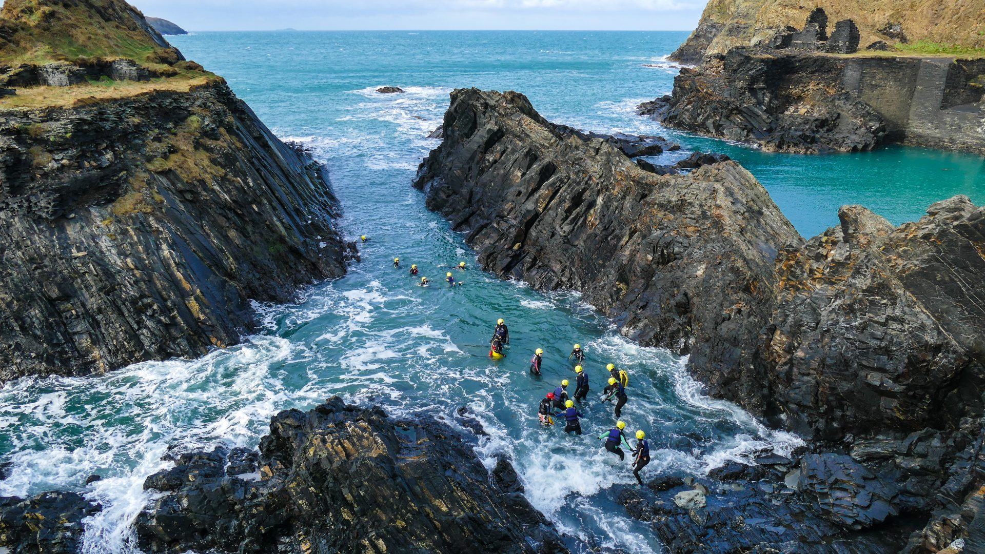 The surrounding views are spectacular for this group of coasteering clients who carefully enter the water.