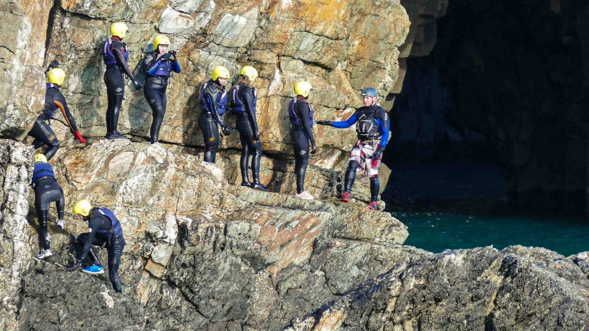 An instructor talks with the group while standing on a rock edge on the coasteering adventure.