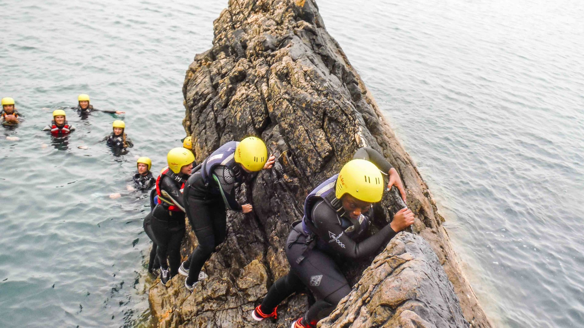 Clients make their way carefully up a rocky ledge on this coasteering adventure.
