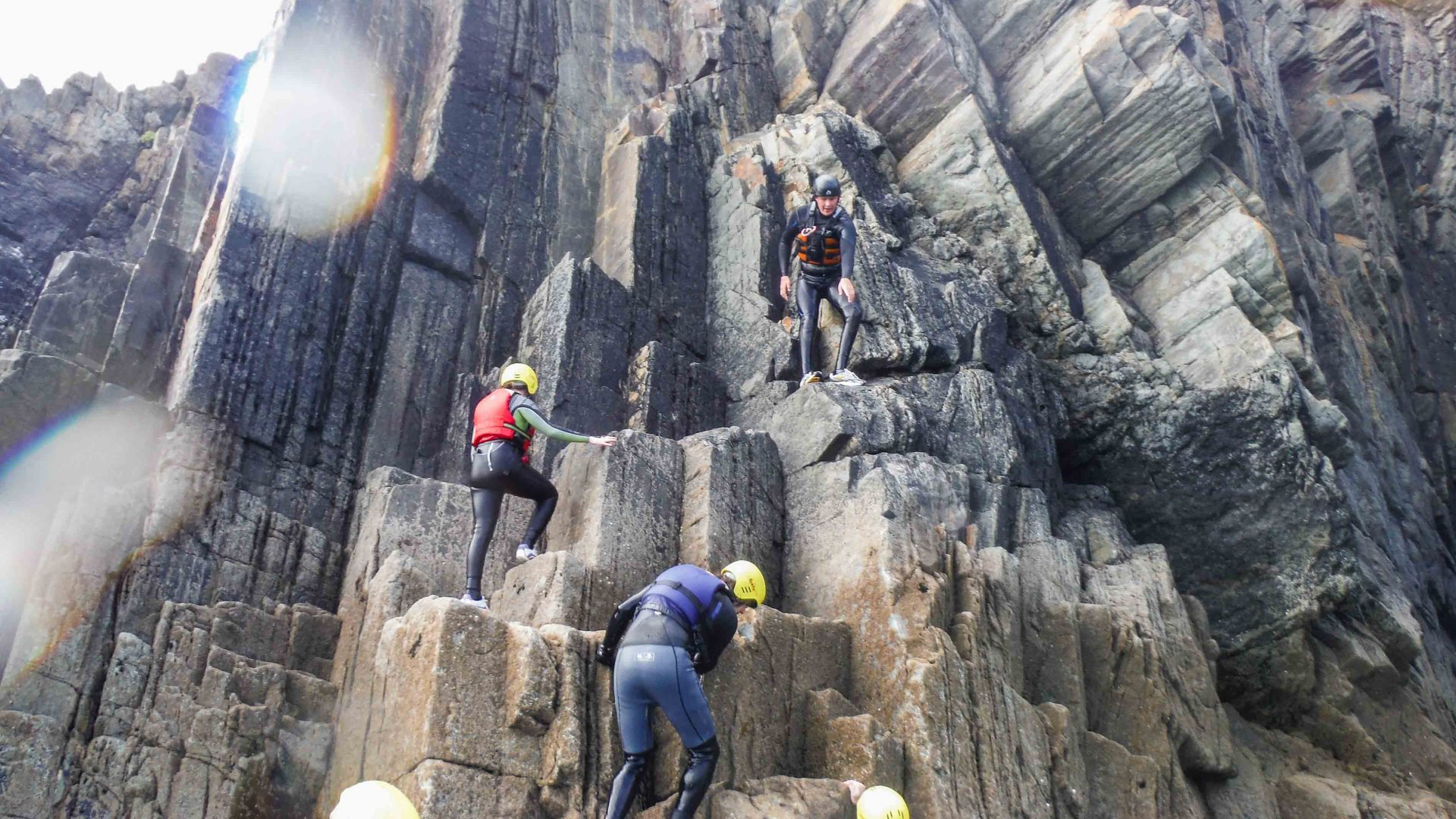 Clients on this coasteering adventure help each other up the tall rocky cliff ahead of them.