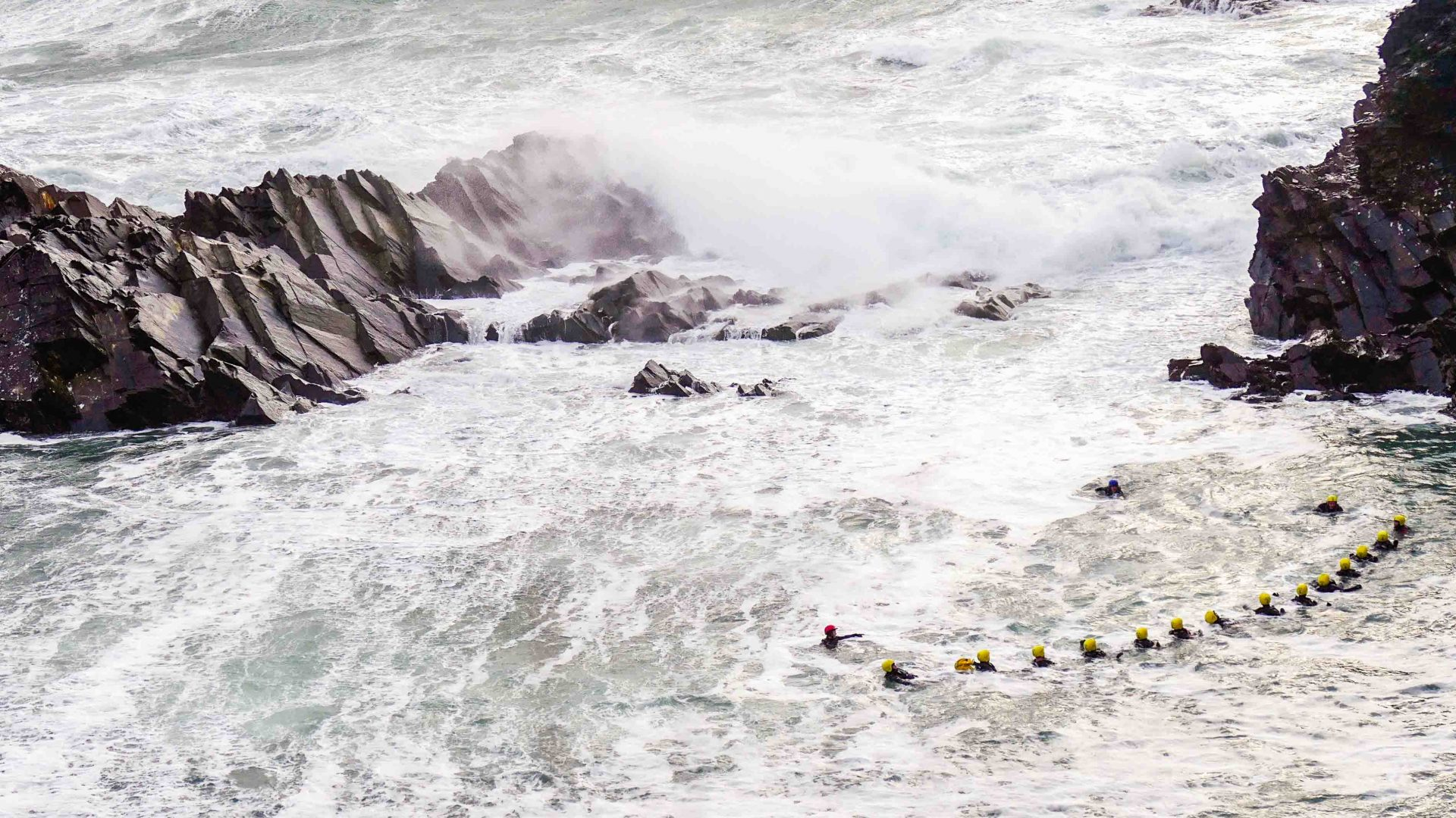 Clients in this coasteering adventure look like mere specks in the white wash of the rough sea off the Welsh coast.