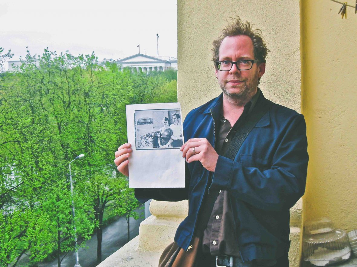 David Farley standing on Lee Harvey Oswald's balcony holding a photo of Oswald who was standing exactly where he was.