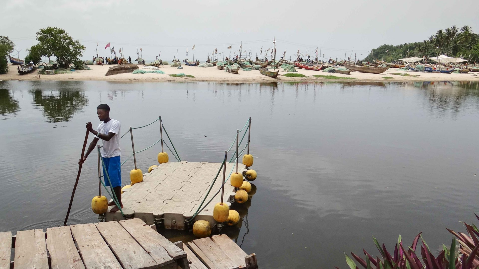A boat man crosses the lagoon in front of White Sands, Ghana.