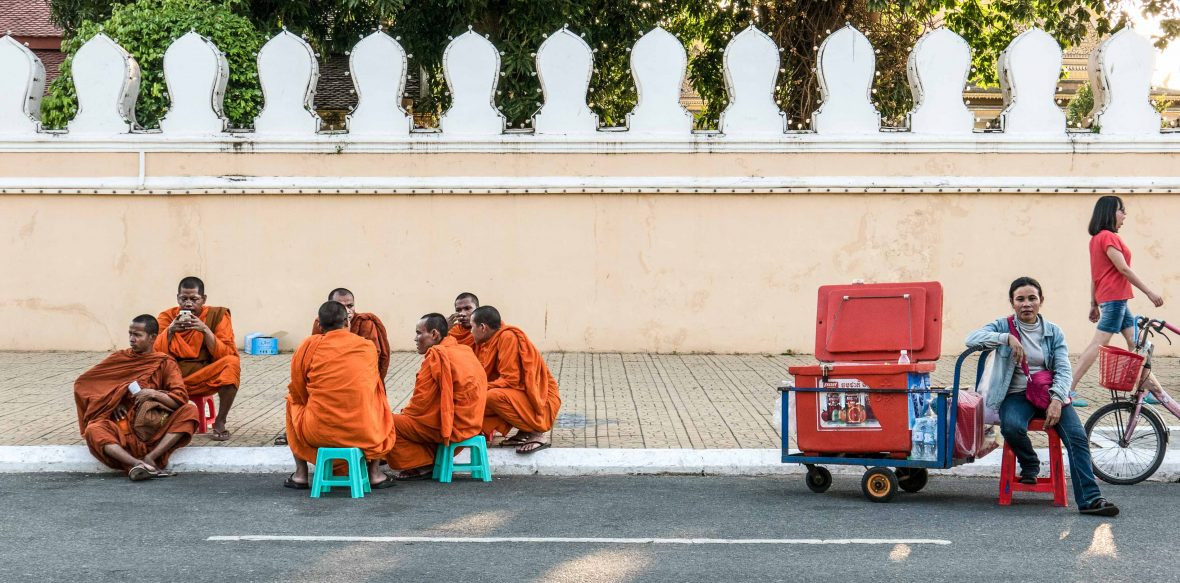 Plastic chairs of Southeast Asia: Monks sit beside the walls of the Royal Place in Phnom Penh, Cambodia.