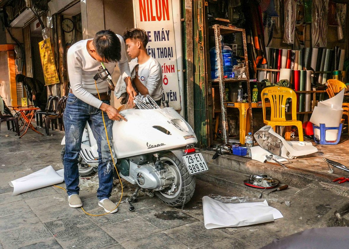 Plastic chairs of Southeast Asia: Fixing scooters in the back streets of many a Vietnam town.