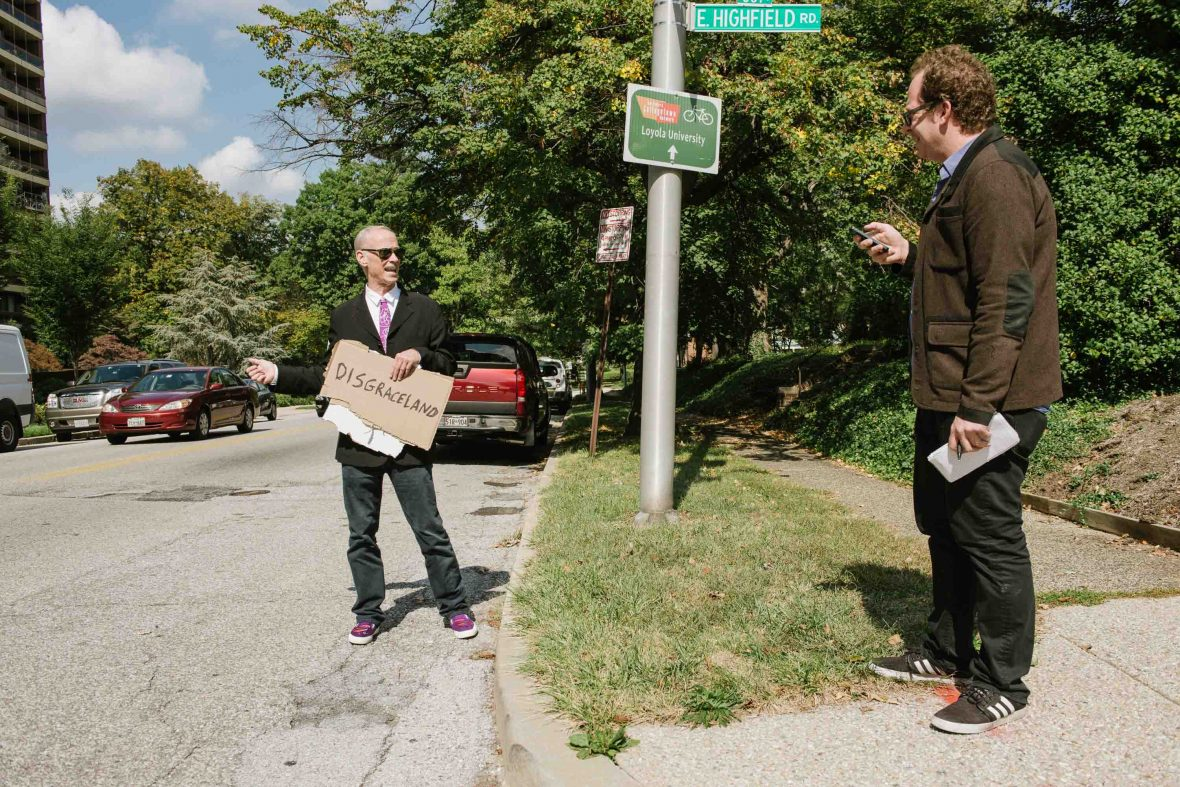 John Waters and travel writer, David Farley, hitchhike in Baltimore, MD.