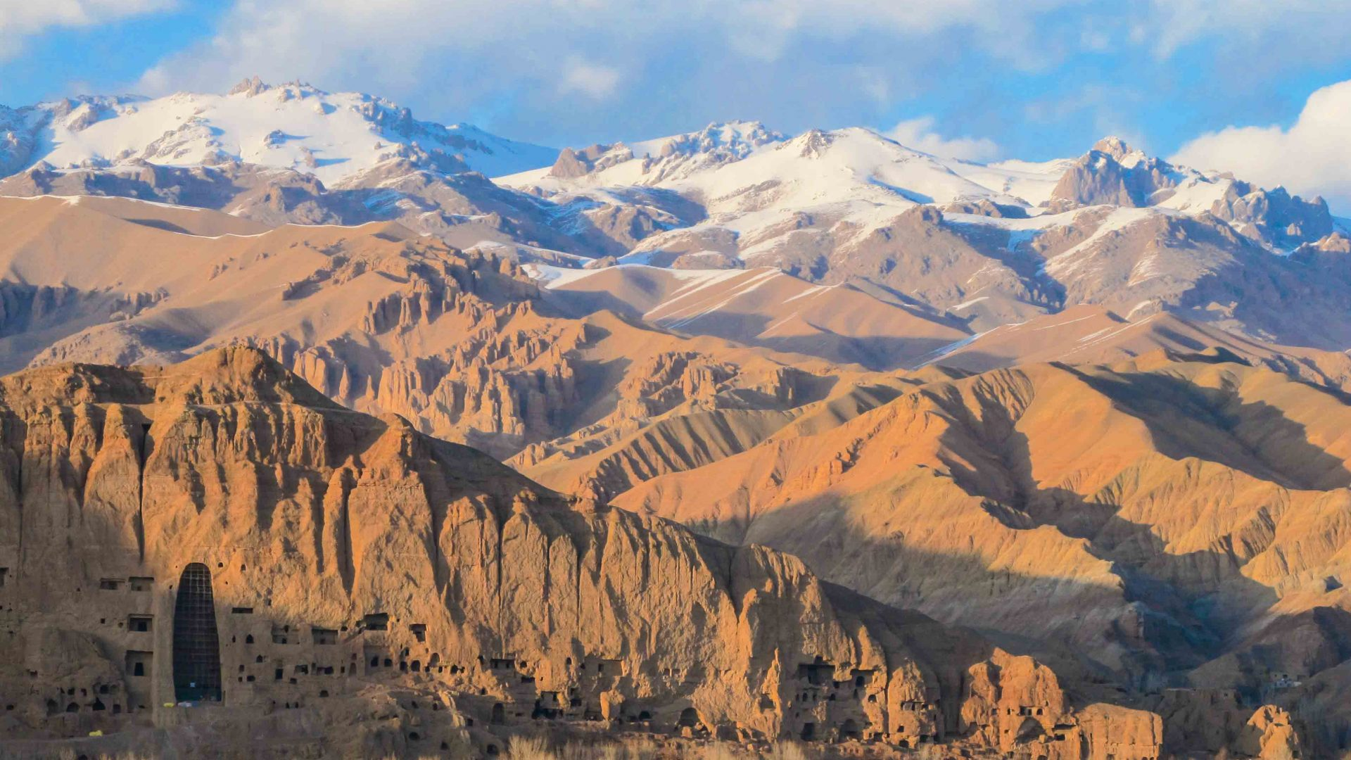Afghanistan's arid mountains backed by snowy mountains.
