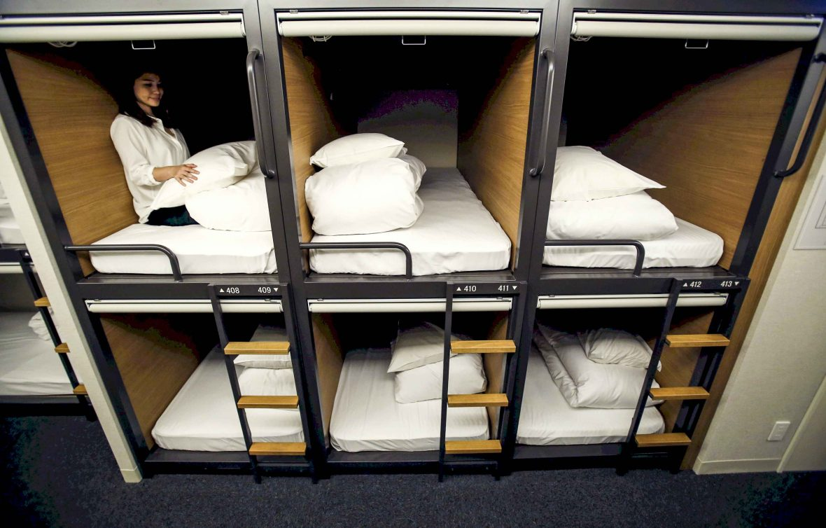 A woman sits inside a one man capsule bed unit.