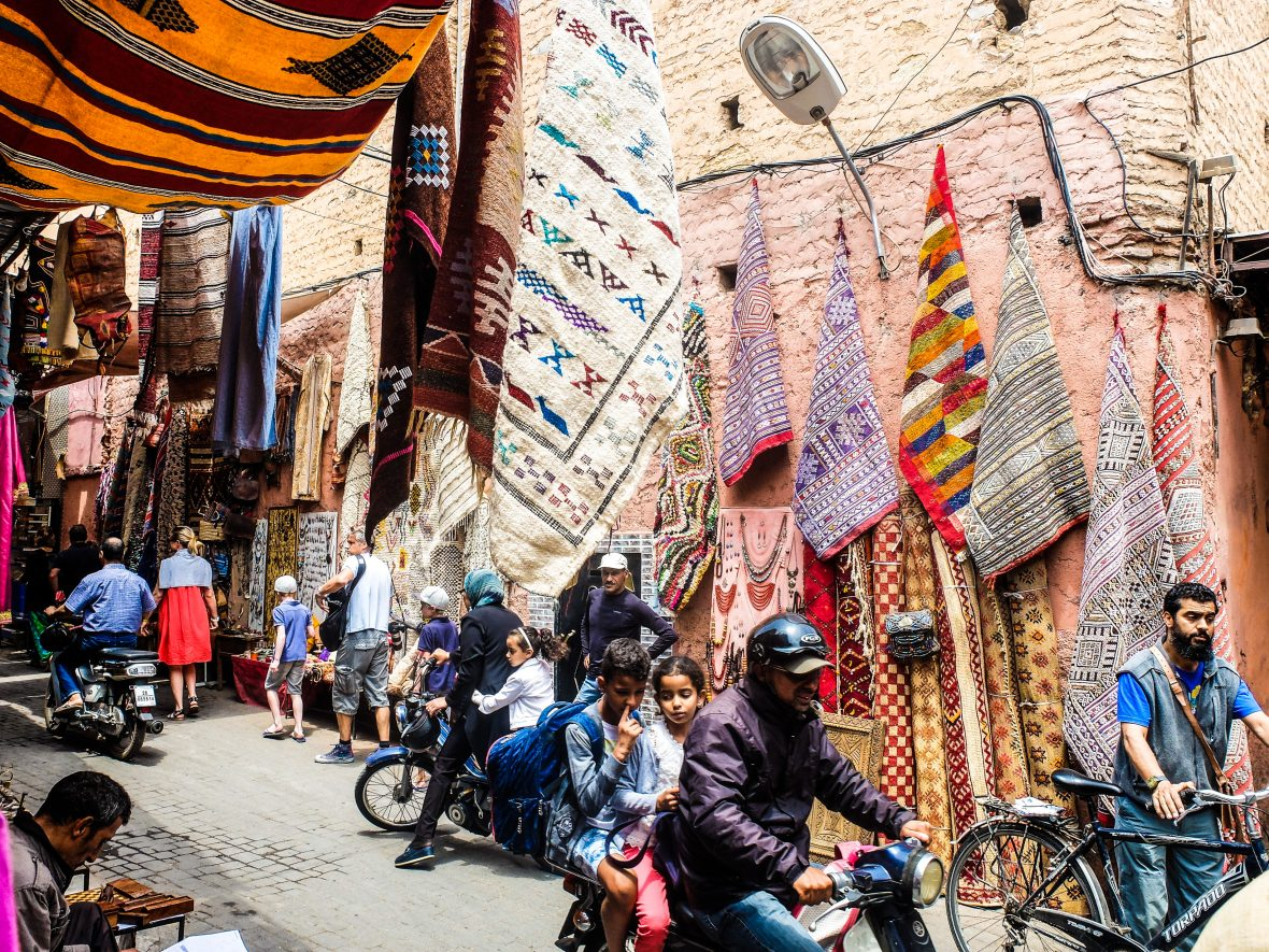 Colorful carpets hang from the walls in a bustling medina in Marrakesh, Morocco.