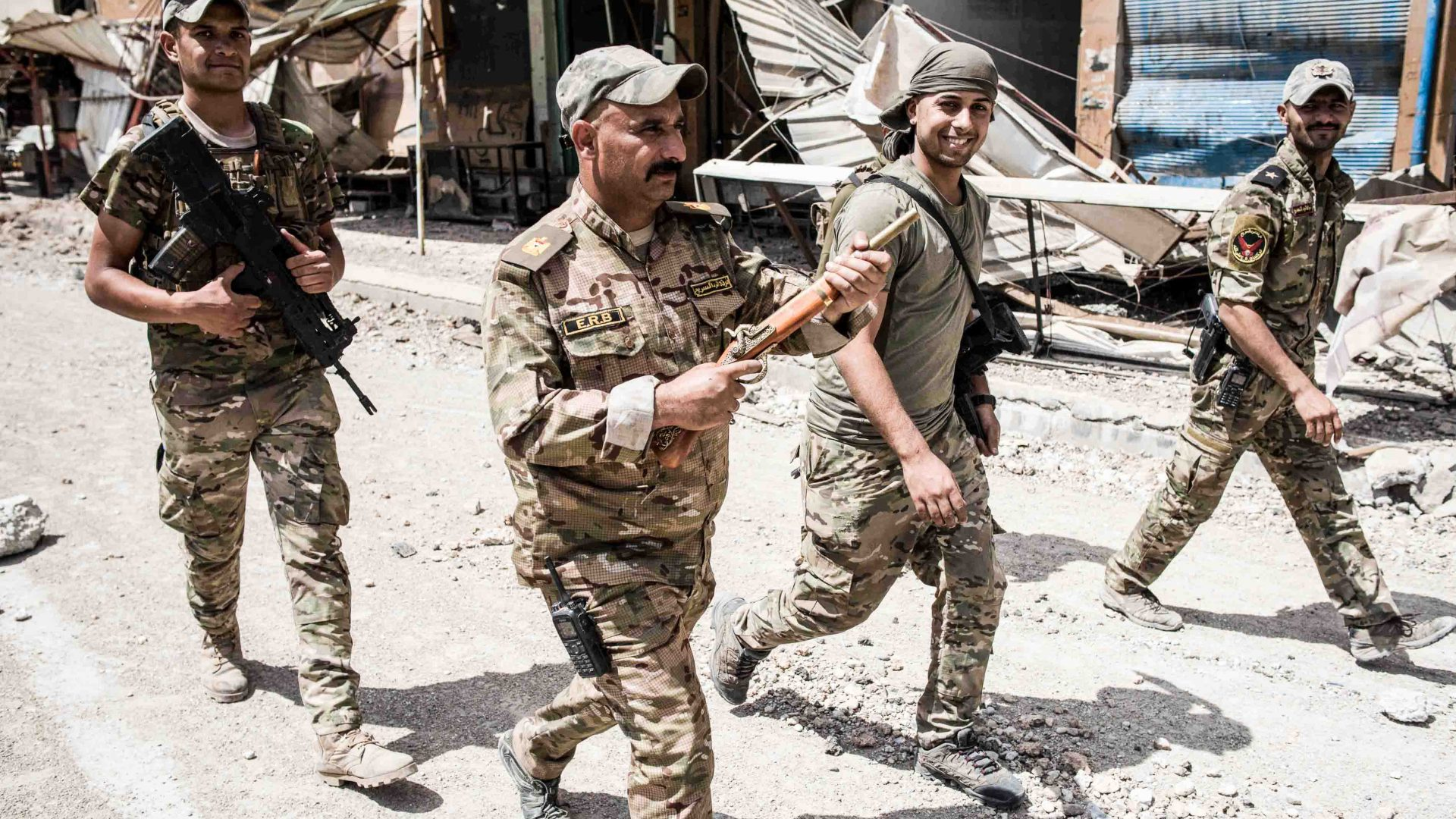 Major Hussein Wali of the Iraqi Emergency Response Division holding a toy gun as he walks through west Mosul with his men, May 2017.