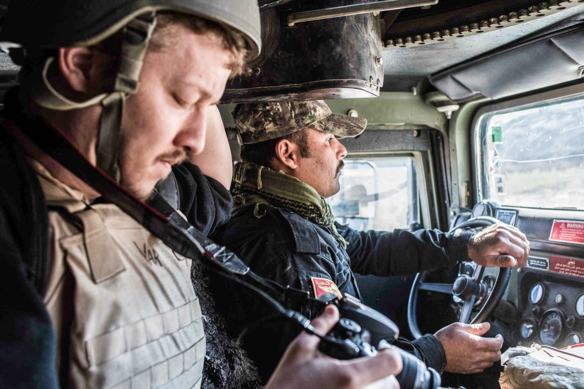 American freelance journalist Igor Kossov with an Iraqi special forces soldier inside an armoured vehicle in Mosul on January 17, 2017.