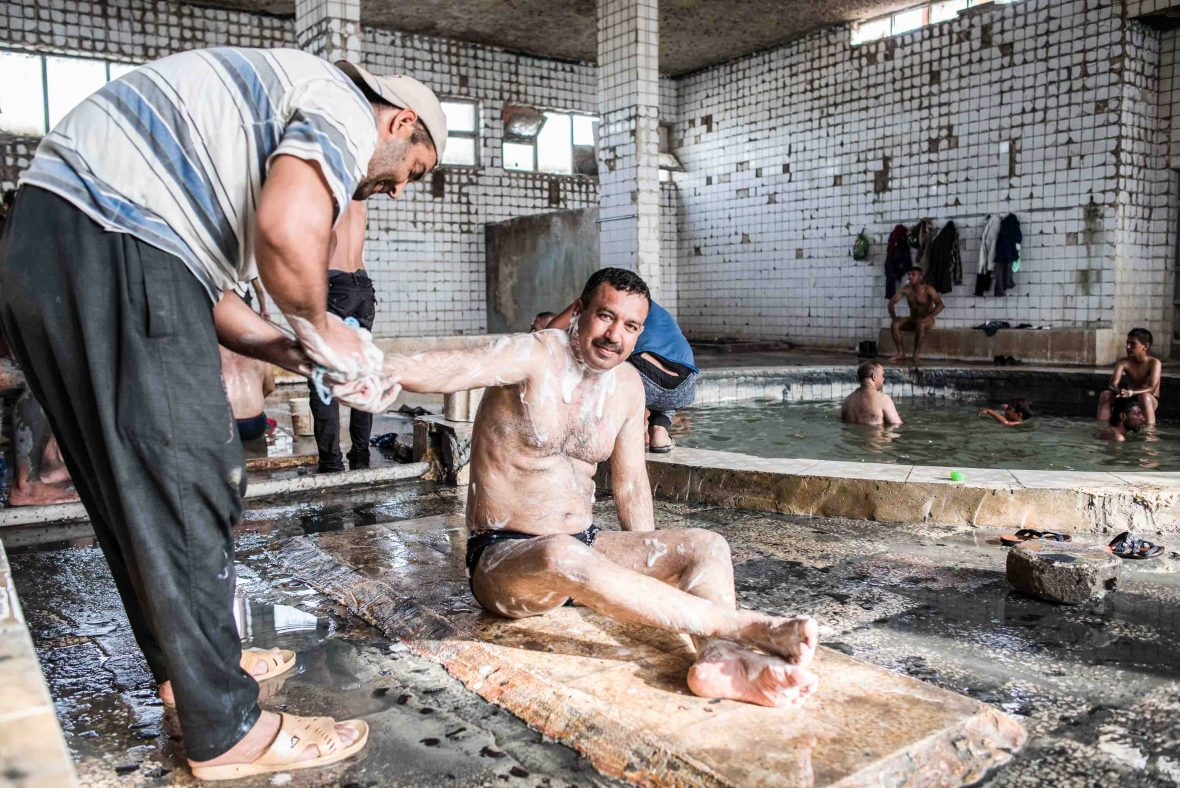 A local man temporarily escapes the stresses of life in a war zone with a scrub in the Hammam Al-Alil sulphur spa, April 2017.