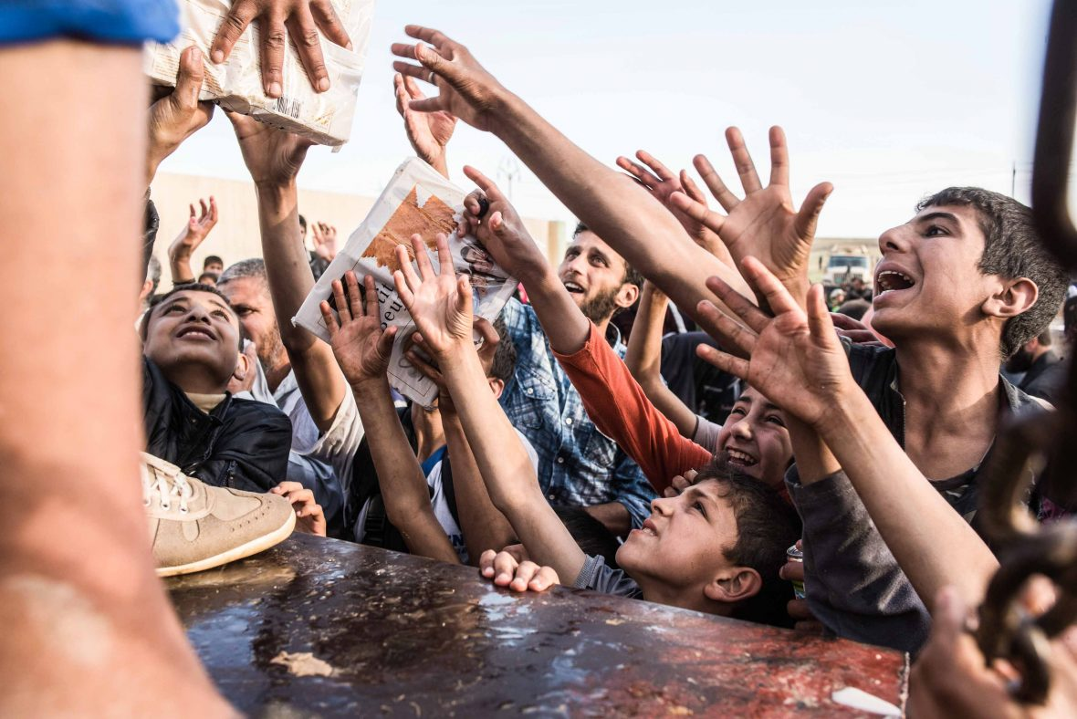 Displaced civilians grab at the food being distributed at an aid centre is Mosul, Iraq.