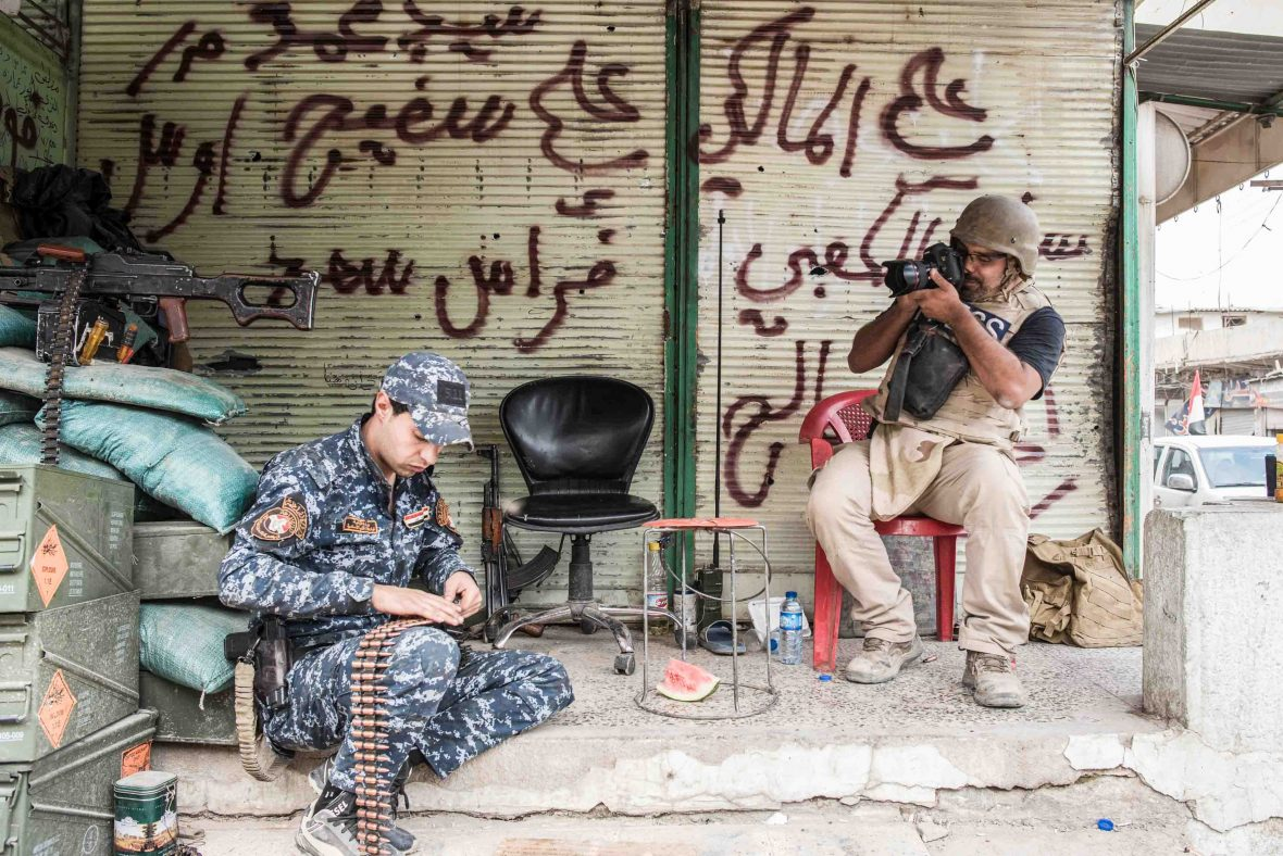 Brazilian freelance journalist, Yan Boechat, photographs an Iraqi federal policeman in west Mosul.